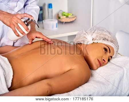 Massage therapy in cosmetology spa centre. Woman therapist making manual therapy back. Hands of masseuse treatment pour oil on patient body of spinal injuries 40 old client in spa salon.