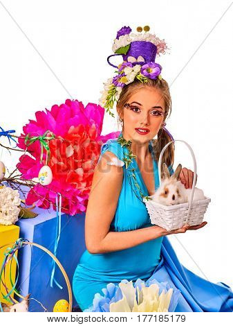 Easter dresses for women. Girl touch bunny . Woman with holiday hairstyle and make up holding rabbit in eggs basket with flowers. Adults at festival. Breeding of domestic animals.