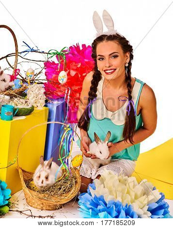 Easter bunny ears headband for women. Girl holding basket bunny and eggs. Woman with holiday hairstyle and make up touch rabbit with flowers. Adults at festival. Breeding of domestic animals.