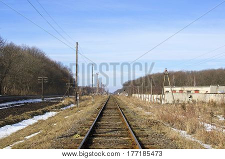 Railroad track and electric posts on blue sky background