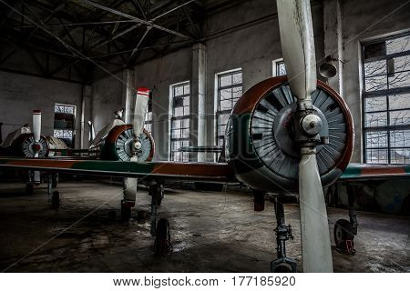 A series of broken old sports aircraft in a hangar in the evening. Engine oil is drained from the aircraft screws into the jars.