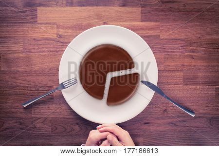 Market share - marketing business concept. Business visual metaphor - businessman with plate and pie chart with imitation of a chocolate cake.