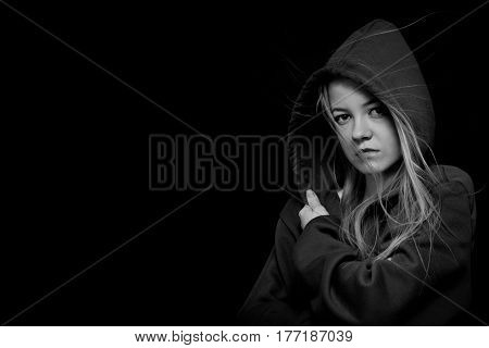 scared girl in hood looking at camera on black background monochrome