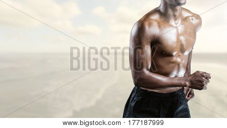 Digital composite of Fitness Torso against sea in background