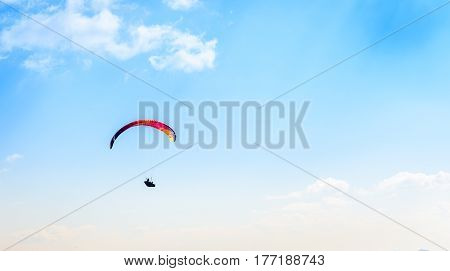 Paraglider Flying Against The Blue Sky With White Clouds.