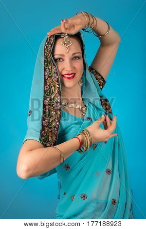 beautiful woman in Indian dress posing on blue background