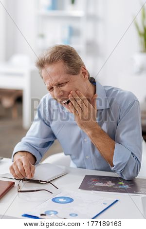 Bad toothache. Poor male person wearing blue shirt wrinkling his forehead putting his elbows on the table