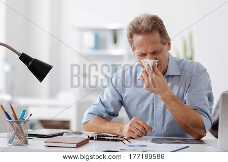 Awful allergy. Bad looking man sitting at the table holding white napkin near his nose while keeping eyes closed