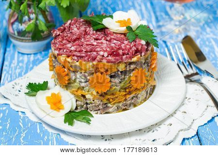 Multilayer festive salad with beef pickled cucumbers and carrots on a blue wooden table