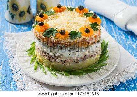 Multilayer festive salad with tuna vegetables and eggs on a blue wooden table