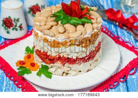 Multilayer festive salad with chicken peppers and beans on blue wooden table. The idea of a holiday recipe for Mother's Day