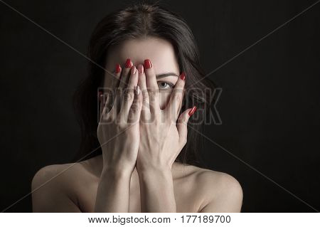 woman cover her face on black background