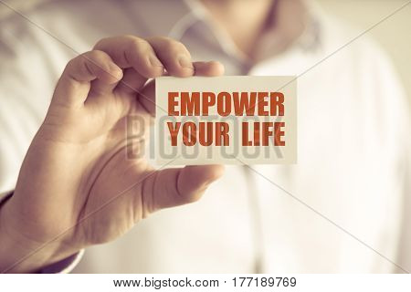 Businessman Holding Empower Your Life Message Card