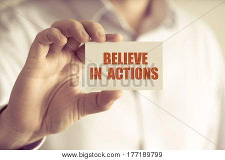 Businessman Holding Believe In Actions Message Card