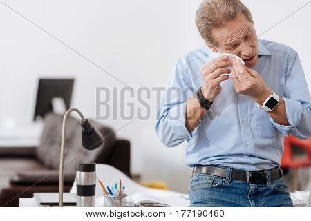 Need a vacation. Frustrated middle-aged man keeping eyes closed and mouth opened wearing smart blue shirt while standing before his working place