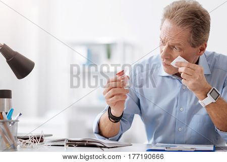 Take it. Sick man wearing blue shirt holding jar with tablets in right hand and keeping his left hand with napkin on the cheek