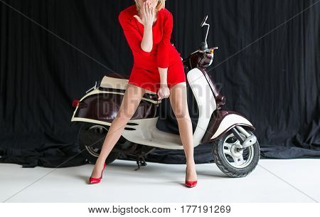 the charming sexy young woman in a short red dress and red shoes standing in the moped background in studio. Retro shot. Fashion art photo.