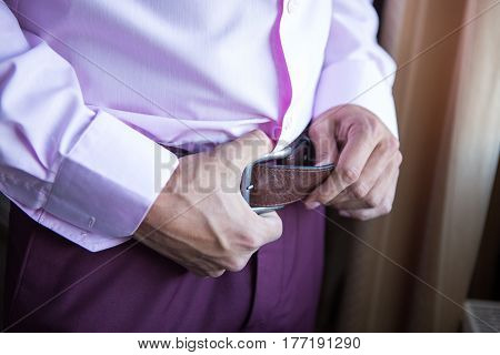 Accessories for the groom. The groom buckles the belt on his trousers. Wedding detail.