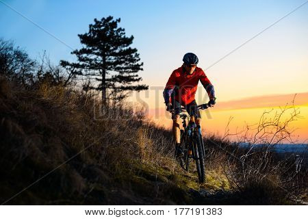 Enduro Cyclist Riding the Mountain Bike on the Rocky Trail at Sunset. Active Lifestyle Concept. Free Space for Text.