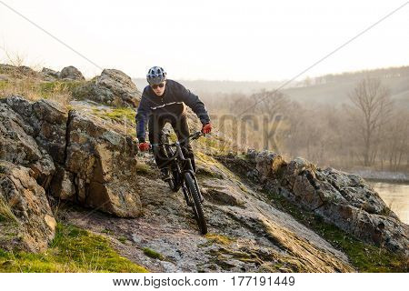 Enduro Cyclist Riding the Mountain Bike Down Beautiful Rocky Trail. Extreme Sport Concept. Free Space for Text.