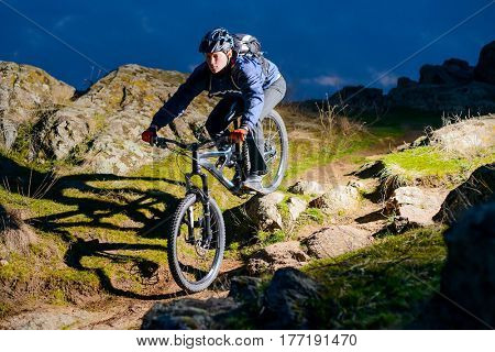Enduro Cyclist Riding the Bike on the Rocky Trail at Night. Extreme Sport Concept. Free Space for Text.