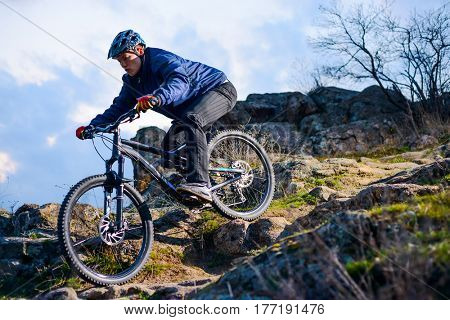 Cyclist Riding the Bike on the Rocky Trail at Sunset. Extreme Sport Concept. Free Space for Text.