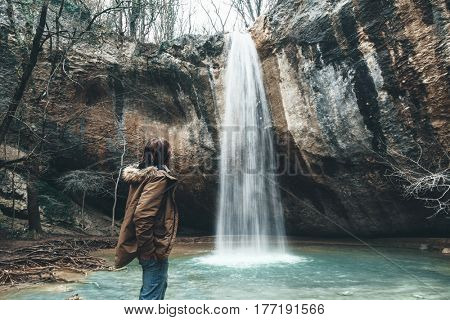 Traveler standing by the waterfall and looking at it. Cold weather, winter hiking. Wanderlust photo series.