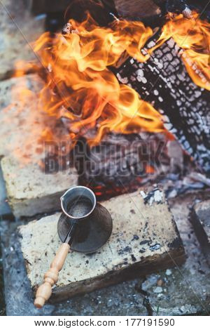 Turkish coffee in turk pot by the fire. Camping detail, travel lifestyle photo.