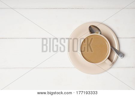 top view of cup of coffee with milk or flat white on wooden background with copy space