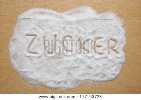 Zucker, meaning sugar in German, written in sugar spread out on kitchen table
