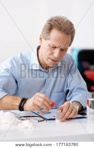 Do your best. Concentrated male person wearing blue shirt, having bracelet and watches on his hands wrinkling his forehead