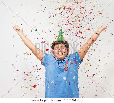 Happy kid celebrating party with blowing confetti
