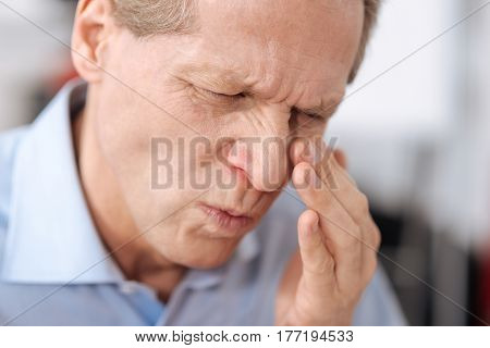 Feeling discomfort. Portrait of serious man wrinkling his nose keeping eyes closed touching cheek