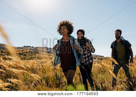 Group of friends on walk through countryside together. Happy young men and women hiking together on a summer day.