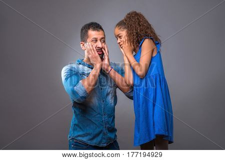 A young black man kneeling next to his daughter and they both surprised and covering their mouth with their hands