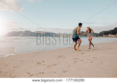 Fit Young Couple Playing On The Beach