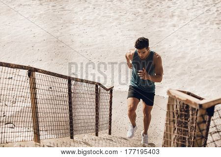 Fit young man running up the staircase on beach. Young male runner working out on steps on sea shore.