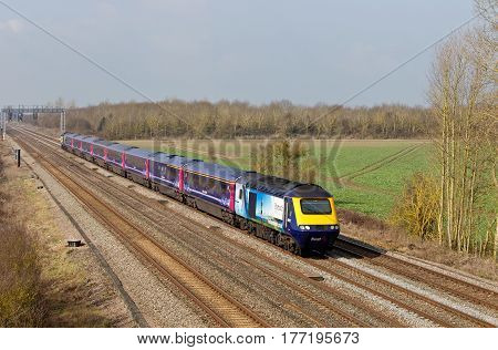 DENCHWORTH, UK - MARCH 25: A special liveried FGW HST passenger train heads towards London Paddington on March 25, 2015 in Denchworth. FGW operate at 208 stations over an operating distance of 2130 km