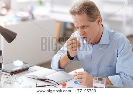 It is workday. Worried man wearing blue shirt, wrinkling his nose while looking sideways