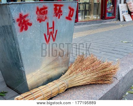 Beijing, China - Oct 30, 2016: Roadside metal rubbish bin and straw broom along a street in Old Beijing. Chinese characters on bin mean