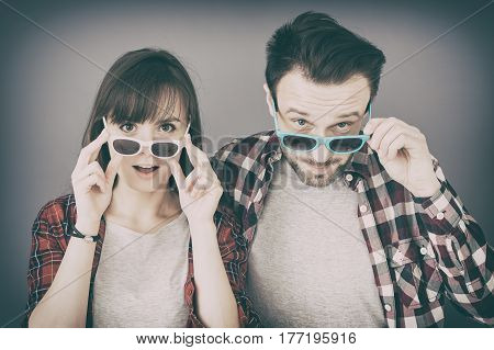 A pair of young people leave glasses and opens her mouth in surprise. They are surprised and amazed they have to face the WOW effect.