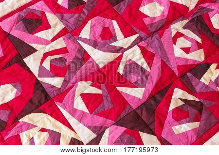 Part of color patchwork quilt with purple flowers pattern as background. Pink Scrappy blanket. Hobby Concept. Handmade.