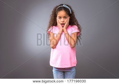A young black teenage girl standing and looking surprised