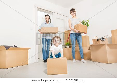 Young family with a child moves to a new apartment. Parents and daughter are happy. The girl pushes box. The concept of a new home.
