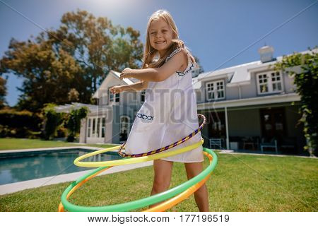 Happy little girl rotating hula hoop outdoors in her backyard. Beautiful little girl having fun with hula hoops outdoors.
