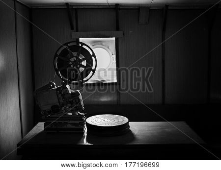 Black and white picture of an old cine-projector standing on a table. Film reels laying on a table.