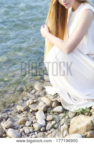 Beautiful bride by the mountain river at sunrise. Close up