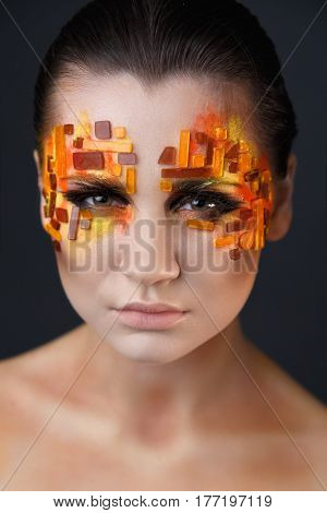 Girl With Orange And Red Rhinestones On Her Face.