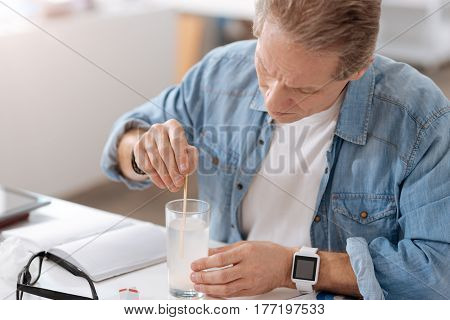 Be on style. Serious elderly male wearing jeans shirt, wrinkling his forehead while holding glass in left hand