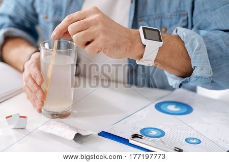 Look at details. Sick man holding glass on the table having watches on the left hand while keeping wooden stick in fingers